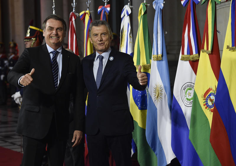 Argentina's President Mauricio Macri, right, gives a thumbs up to photographers with Brazil's President Jair Bolsonaro during a photo opportunity at the Mercosur Summit in Santa Fe, Argentina, Wednesday, July 17, 2019. The South American trading bloc that includes founding members Brazil, Argentina, Paraguay, and Uruguay, is one of the world's largest. (AP Photo/Gustavo Garello)