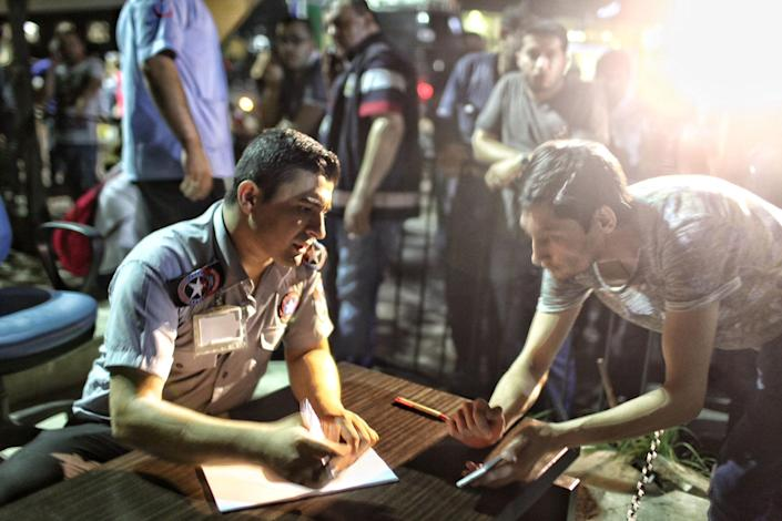 <p>Turkish health officials make the lists of the Ataturk Airport suicide bomb attack victims outside Bakirkoy Sadi Konuk Hospital, in the early hours of June 29, 2016 in Istanbul, Turkey. (Defne Karadeniz/Getty Images) </p>