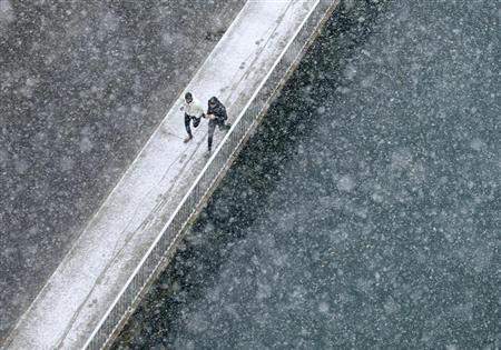 Joggers run along the embankment of Aare river during the first snowfall in Bern