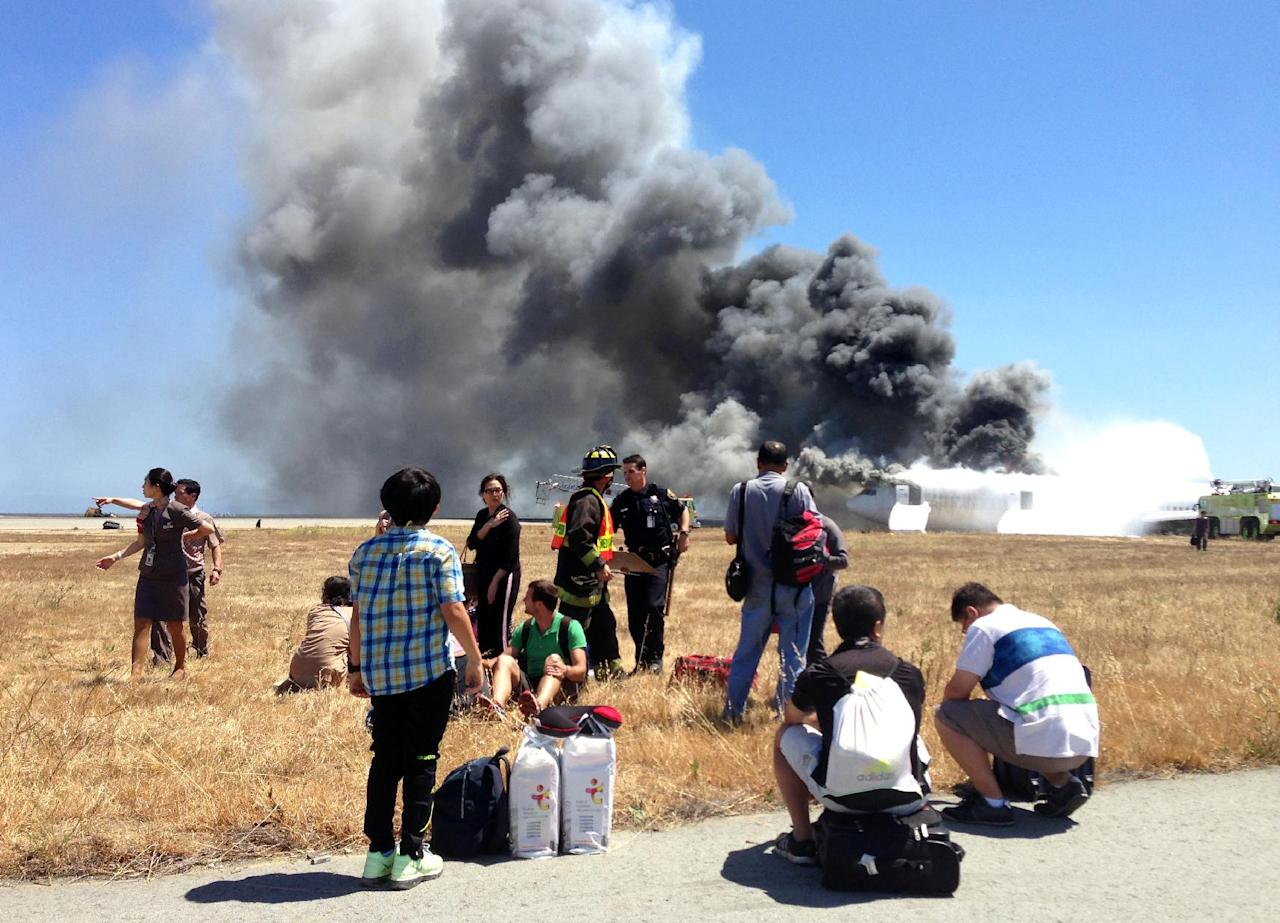 FILE - This Saturday, July 6, 2013, file photo provided by passenger Benjamin Levy, shows fellow passengers from Asiana Airlines flight 214, many with their luggage, on the tarmac just moments after the plane crashed at the San Francisco International Airport in San Francisco. The National Transportation Safety Board says it is now planning to hold its hearing Wednesday, Dec. 11, 2013, into the crash-landing of the jet that left three Chinese teens dead. (AP Photo/Benjamin Levy, File)