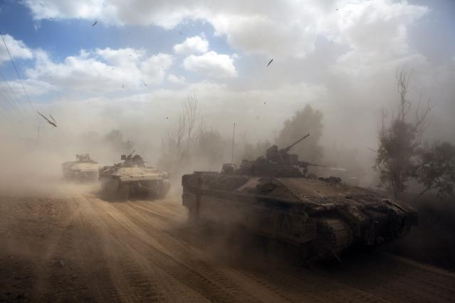 Israeli APCs drive near the Israeli border with Gaza as the come out of the Gaza Strip July 25, 2014. A flurry of long-range rocket launches on Friday set off sirens around Israel's commercial capital of Tel Aviv, where witnesses reported several interceptions by the Iron Dome air defence system. A building was hit in the southern coastal town of Ashkelon but there were no casualties. Gaza officials said Israeli strikes killed 19 people on Friday. They put the number of Palestinian deaths in 18 days of conflict at 808, most of them civilians. REUTERS/Nir Elias (ISRAEL - Tags: POLITICS CIVIL UNREST MILITARY CONFLICT TPX IMAGES OF THE DAY)
