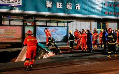 An enormous sinkhole swallowed passers-by and a public bus in northwest China, reported state media - Credit: AFP