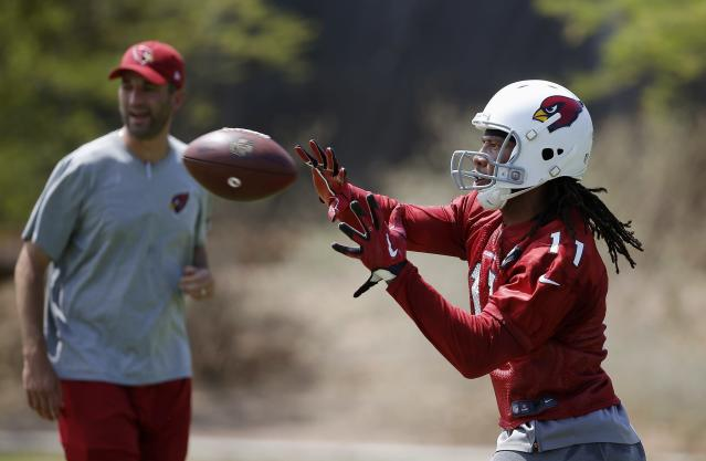 Arizona Cardinals' Larry Fitzgerald (11) makes a catch as wide receivers coach Kevin Garver, left, watches during the NFL football team's practice Thursday, June 14, 2018, in Tempe, Ariz. (AP Photo/Ross D. Franklin)