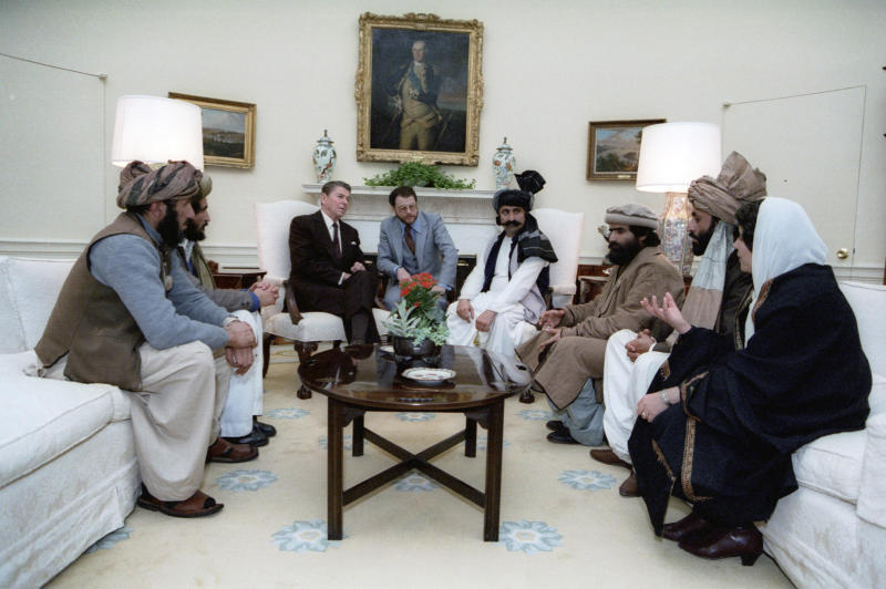 """UPDATES INFORMATION - In this photo courtesy Ronald Reagan Library, then President Ronald Reagan meets with Afghan """"freedom fighters"""" on Feb. 2, 1983, in the Oval Office of the White House in Washington, to discuss Soviet atrocities in Afghanistan.  The Taliban did not emerge until 1994. A Twitter user posted the photo on Sept.7, 2019 with a caption implying that Reagan met with the Taliban: """"NeverTrumpers: A President meeting with the Taliban, this is horrific!"""" The miscaptioned photo circulated prominently on Twitter and Facebook after it was revealed that President Donald Trump planned to meet with Taliban leaders and Afghan officials at the presidential retreat in Camp David, Maryland, just days before the 9/11 anniversary.  (Courtesy Ronald Reagan Library via AP)"""