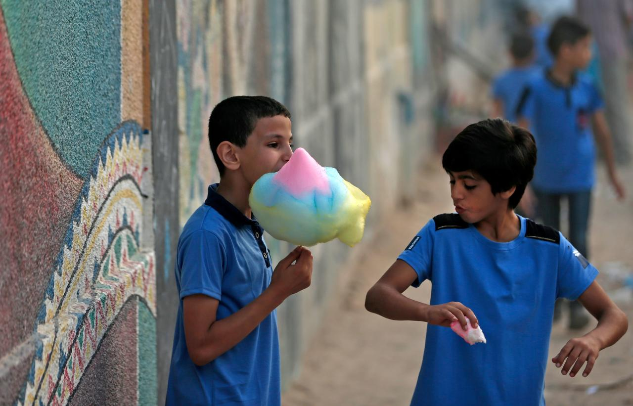 <p>Pupils eat candy floss in front of a school run by the United Nations Agency for Palestinian Refugees (UNRWA) in Gaza City on August 29, 2018, on the first day of classes after the summer holidays. – US President Donald Trump cut of more than $200 million in aid for Gaza and the West Bank this month after earlier freezing of $300 million in annual funding for the UNRWA. (Photo by MAHMUD HAMS/AFP/Getty Images) </p>