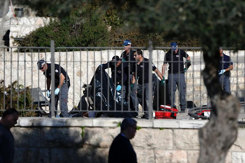 Israeli policemen cover the body of a Palestinian man with a plastic bag following an attack at Damascus Gate in Jerusalem on February 3, 2016 (AFP Photo/Ahmad Gharabli)