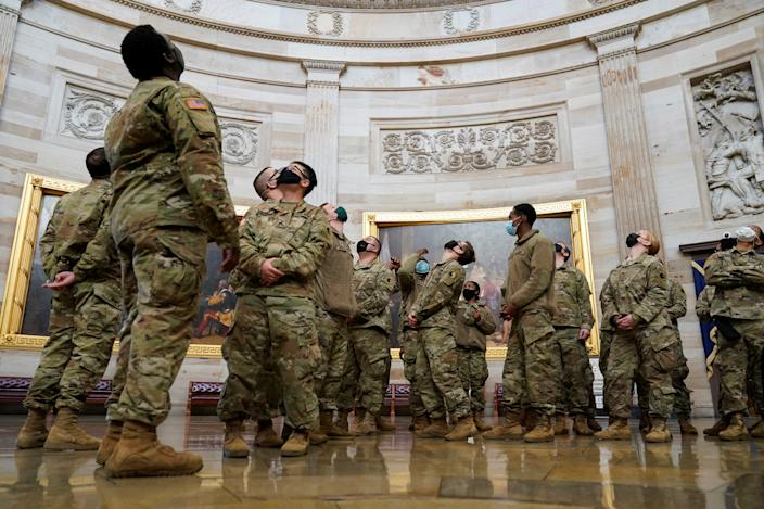 National Guard members crane their necks to look at the ceiling of the Capitol