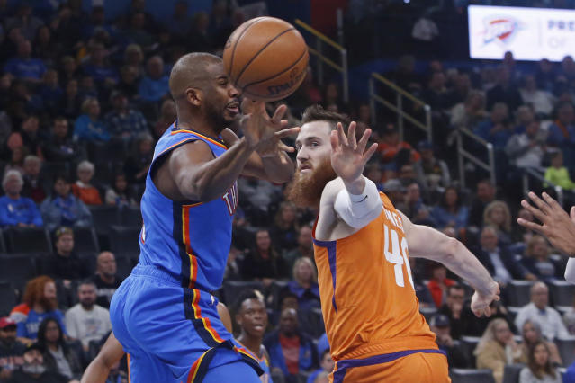 Oklahoma City Thunder guard Chris Paul, left, passes the ball next to Phoenix Suns center Aron Baynes (46) during the first half of an NBA basketball game Friday, Dec. 20, 2019, in Oklahoma City. (AP Photo/Sue Ogrocki)