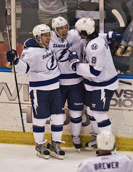 Tampa Bay Lightning's Nikita Kucherov, center, celebrates his game-winning goal with Tyler Johnson, left, and Mark Barberio (8) during overtime of an NHL preseason hockey game against the Florida Panthers on Thursday, Sept. 26, 2013, in Estero, Fla. The Lightning won 3-2. (AP Photo/Steve Nesius)