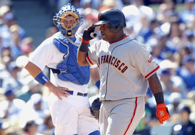 San Francisco Giants' Pablo Sandoval , right, salutes teammates after he hit a three-run home run as Los Angeles Dodgers catcher A.J. Ellis, left, looks on in the fifth inning of a baseball game on Saturday, April 5, 2014, in Los Angeles. (AP Photo/Alex Gallardo)