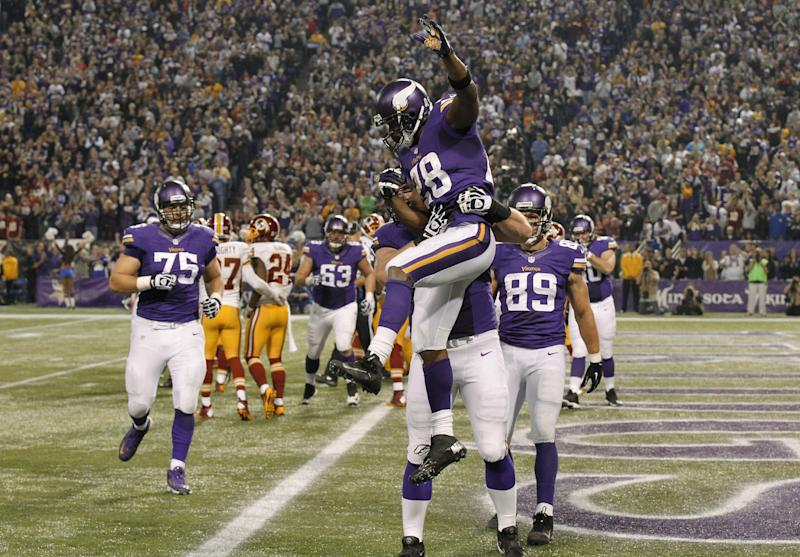 Minnesota Vikings running back Adrian Peterson, center, celebrates with teammates after scoring on a 1-yard touchdown run during the second half of an NFL football game against the Washington Redskins, Thursday, Nov. 7, 2013, in Minneapolis. (AP Photo/Ann Heisenfelt)