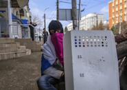 A masked pro-Russian activist looks at a photographer as he rests next to barricades at the Ukrainian regional office of the Security Service in Luhansk, 30 kilometers (20 miles) west of the Russian border, in Ukraine, Wednesday, April 9, 2014. Ukrainian Interior Minister Arsen Avakov said the standoff in Luhansk and the two neighboring Russian-leaning regions of Donetsk and Kharkiv must be resolved within two days. (AP Photo/Igor Golovniov)