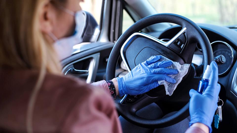 Woman in the car with protective glove and facial mask.