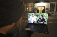 A man watches his laptop showing an interview of Prince Harry and Meghan, The Duchess of Sussex, by Oprah Winfrey outside King Edward VII's Hospital where the Duke of Edinburgh has been transferred from a specialist cardiac hospital to a private facility to continue his recovery after a heart procedure, in London Monday, March 8, 2021. (Yui Mok/PA via AP)