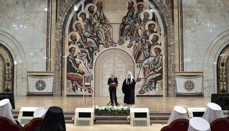 Russian President Vladimir Putin, accompanied by Patriarch Kirill, at a congress of Orthodox bishops at Moscow's Cathedral of Christ the Saviour