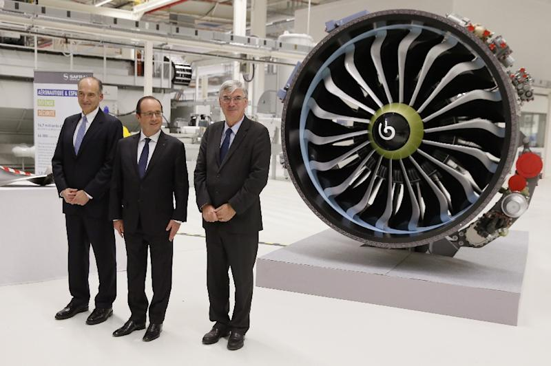 "French President Francois Hollande (C) poses with the CEOs of US technical group Albany, Joseph G. Morone (L) and of French aerospace engineering company Safran, Jean-Paul Herteman, in front of a ""LEAP"" engine at the Safran-Albany plant last year (AFP Photo/Patrick Kovarik)"