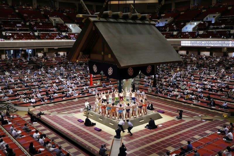 Spectators are seen as sumo wrestlers hold a ring-entering ceremony at the July Grand Sumo Tournament in Tokyo