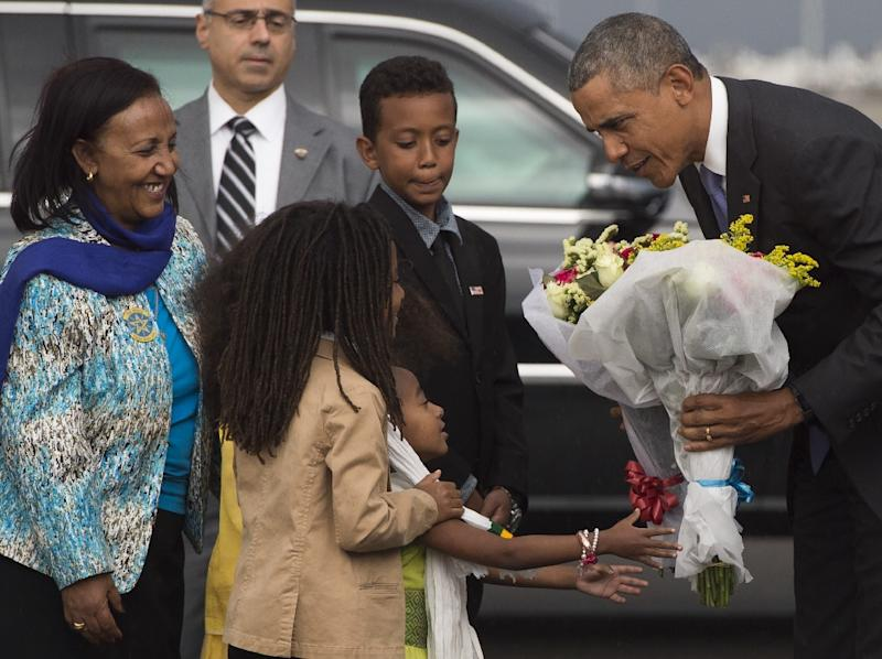 US President Barack Obama receives flowers upon his arrival at Bole International Airport in Addis Ababa, on July 26, 2015 (AFP Photo/Saul Loeb)