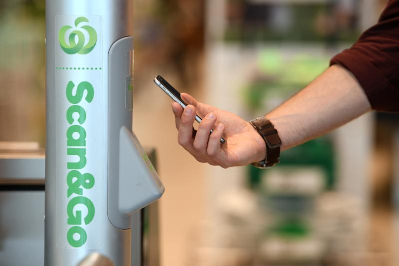 Woolworths employee Bryn Rayfield uses the company's new Scan & Go app at the Double Bay store in Sydney.