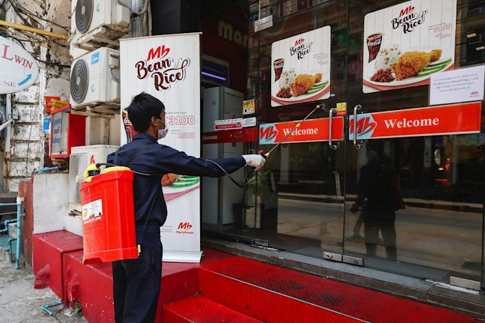 """A member of Yangon City and Development Committee sprays disinfectant on a restaurant's front doors on March 29, 2020. <p class=""""copyright"""">AP Photo/Thein Zaw</p>"""
