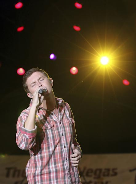 """FILE - This March 30, 2012 file photo shows Scotty McCreery performing at a concert hosted by The Academy of Country Music at the ACM Fremont Street Experience in Las Vegas. The platinum-selling teen and former """"American Idol"""" champ began his freshman year at North Carolina State University recently and he's managed to work out a schedule that allows him to balance his college education with his country music education. (AP Photo/Jeff Bottari, file)"""