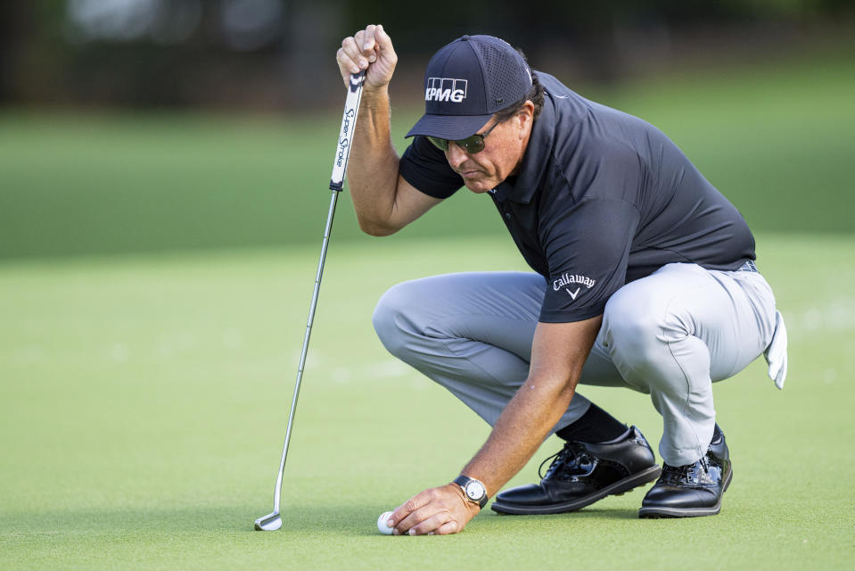 Phil Mickelson lines up his putt on the ninth hole during the first round of the Wells Fargo Championship golf tournament at Quail Hollow Club on Thursday, May 6, 2021, in Charlotte, N.C. (AP Photo/Jacob Kupferman)