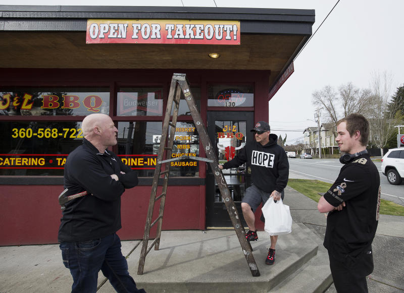 J & L BBQ owner Joel Sexton, left, talks with customer Tony Cecsarini and Austin Eisenhuth, right, after hanging banners announcing the restaurant's ability to accept takeout orders on Tuesday, March 17, 2020 in Snohomish, Wash. (Andy Bronson/The Herald via AP)