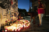 FILE - Friends of Wesley Green light candles at a sidewalk memorial for him, July 28, 2020 in the Ditmas Park neighborhood of New York. Green, 32, was shot and killed near his home the day before. Police recorded 280 killings through Aug. 23. By comparison there were nearly 2,300 murders in New York City in 1990 and in 2000 the number was 673. (AP Photo/Mark Lennihan)