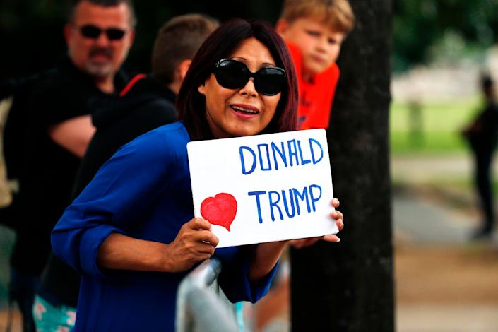 A woman holds a placard in support of Trump as he arrives in Paris.