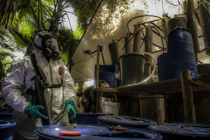 A Sinaloa's state police officer works during the dismantle of one of the three clandestine laboratories producers of synthetic drug, mainly methamphetamine in El Dorado, Sinaloa state, Mexico on June 4, 2019. (Photo by RASHIDE FRIAS / AFP)        (Photo credit should read RASHIDE FRIAS/AFP/Getty Images)