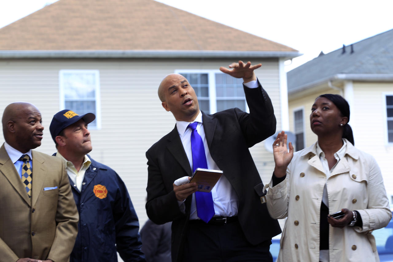 Newark Mayor Cory Booker, second right, has a bandaged right hand in front of a home in Newark, N.J., Friday, April 13, 2012, as he describes the scene Thursday when he rescued a woman from her burning home.  Booker said Friday he feared for his life as he helped rescue a neighbor from a fire before firefighters arrived. He described how he returned home Thursday night and saw his neighbor's home engulfed in flames. The woman Booker helped save is in stable condition. (AP Photo/Mel Evans)