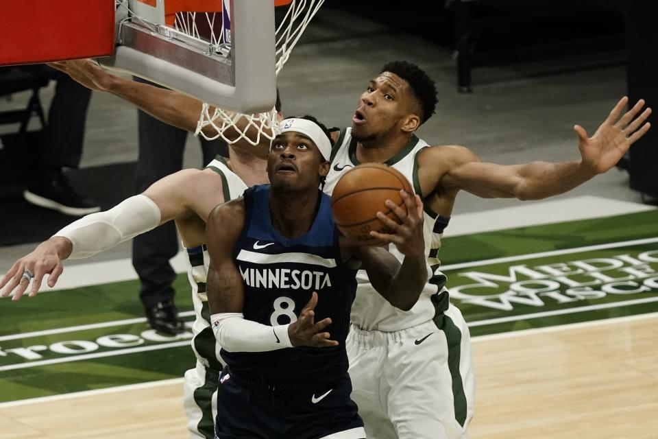 Minnesota Timberwolves' Jarred Vanderbilt shoots past Milwaukee Bucks' Giannis Antetokounmpo during the first half of an NBA basketball game Tuesday, Feb. 23, 2021, in Milwaukee. (AP Photo/Morry Gash)
