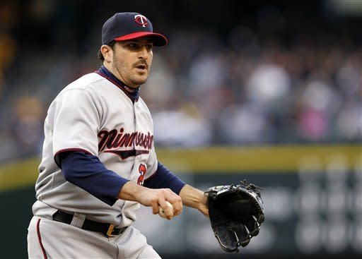 Minnesota Twins starting pitcher Jason Marquis looks to first after fielding a grounder from Seattle Mariners' Dustin Ackley in the sixth inning of a baseball game, Saturday, May 5, 2012, in Seattle. Ackley singled on the play. (AP Photo/Elaine Thompson)