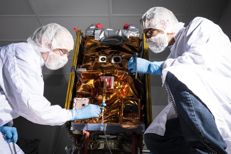 Two engineers working on a small satellite