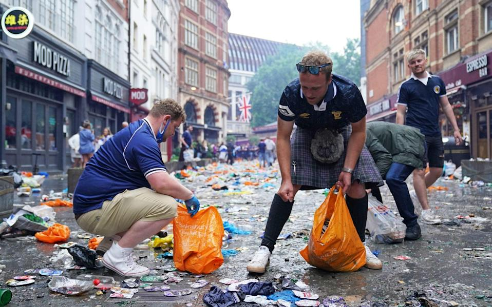 Scotland fans clean up litter in Irving Street near Leicester Square, London, ahead of the UEFA Euro 2020 Group D match between England and Scotland - PA