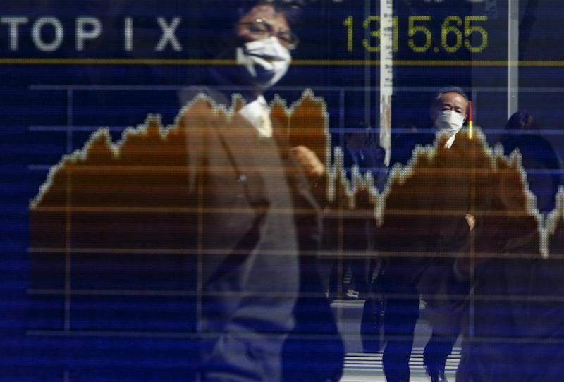 Pedestrians wearing masks are reflected in an electronic board showing the graph of the recent fluctuations of the Tokyo Stock Price Index (TOPIX) outside a brokerage in Tokyo, Japan, February 26, 2016. Asian shares made guarded gains on Friday as a gathering of world finance leaders provided a welter of reassuring comments, but little in the way of actual policy stimulus. REUTERS/Yuya Shino TPX IMAGES OF THE DAY