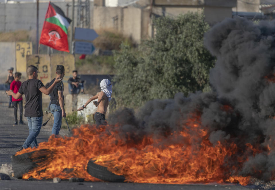 Palestinian protesters burn tires and use slingshots during clashes with Israeli soldiers at the entrance the Jewish settlement of Beit El, background, near the West Bank city of Ramallah, Tuesday, June. 15, 2021. (AP Photo/Nasser Nasser)