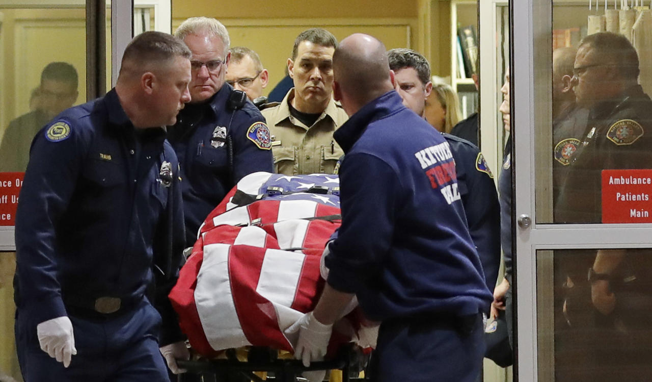 The body of a Kittitas County Sheriff's deputy is draped with a U.S. flag as it is carried out of Kittitas Valley Healthcare Hospital in the early morning hours of Wednesday, March 20, 2019, in Ellensburg, Wash. A sheriff's deputy was killed and a police officer was injured after an exchange of gunfire during an attempted traffic stop. (AP Photo/Ted S. Warren)