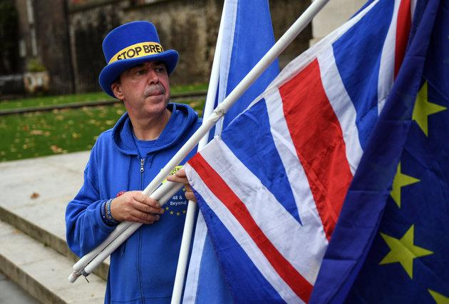 An anti-Brexit demonstrator holds a European Union flag and a British Union flag, also known as a Union Jack, in London Thursday.