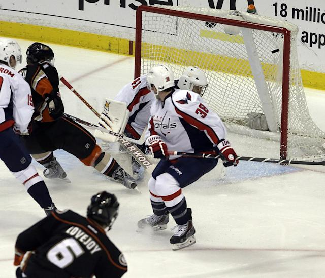 Anaheim Ducks defenseman Ben Lovejoy (6) puts the puck in the net against Washington Capitals goalie Jaroslav Halak (41), of Slovakia, and defenseman Jack Hillen (38) in the first period of an NHL hockey game Tuesday, March 18, 2014. (AP Photo/Reed Saxon)