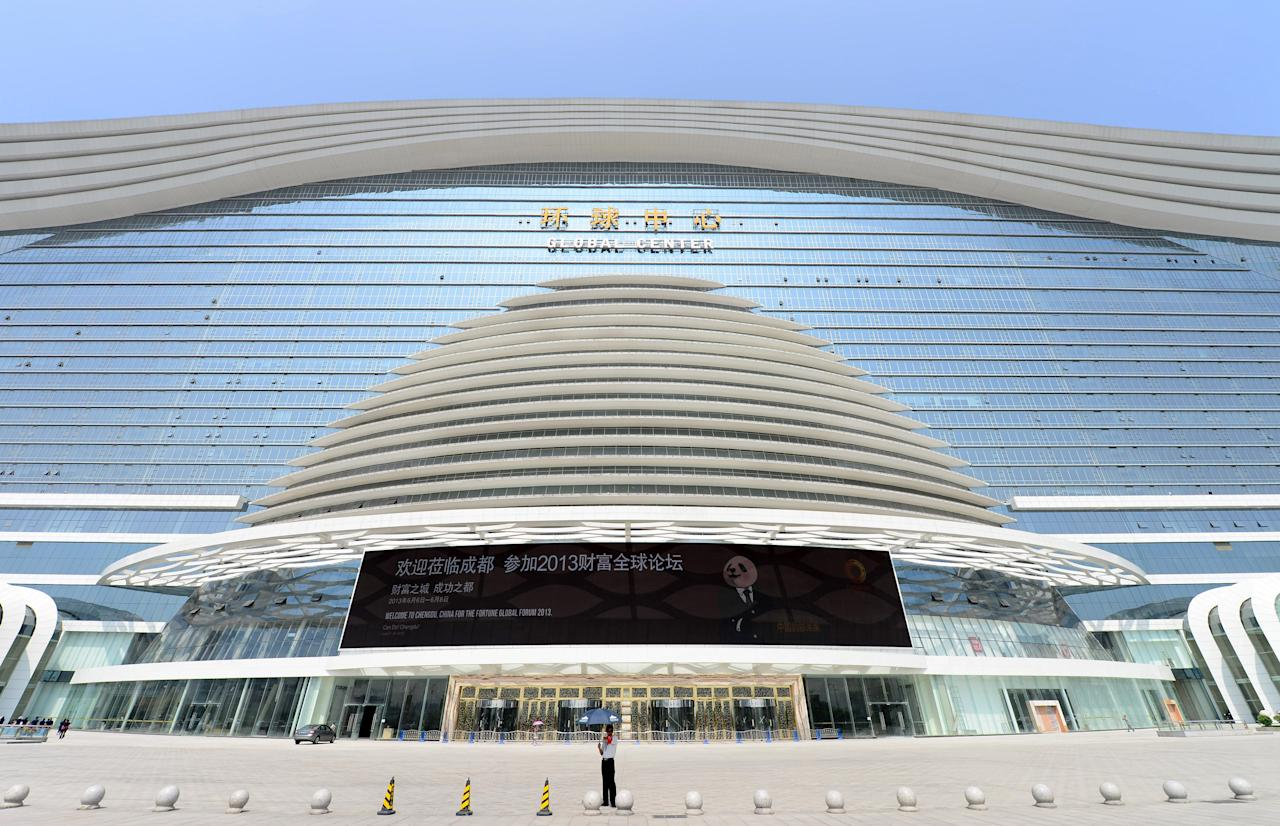 "A man stands before the ""New Century Global Centre"" building in Chengdu, in southwest China's Sichuan province on June 6, 2013.  The center, claimed by Chinese officials as ""the world's largest standalone structure"", is going to be opened to the public on June 28. The 100m high ""New Century Global Centre"" is a symbol of the spread of China's boom: 500m long and 400m wide, with 1.7 million square metres of floor space - big enough to hold 20 Sydney Opera Houses, according to local authorities.  CHINA OUT     AFP PHOTO"