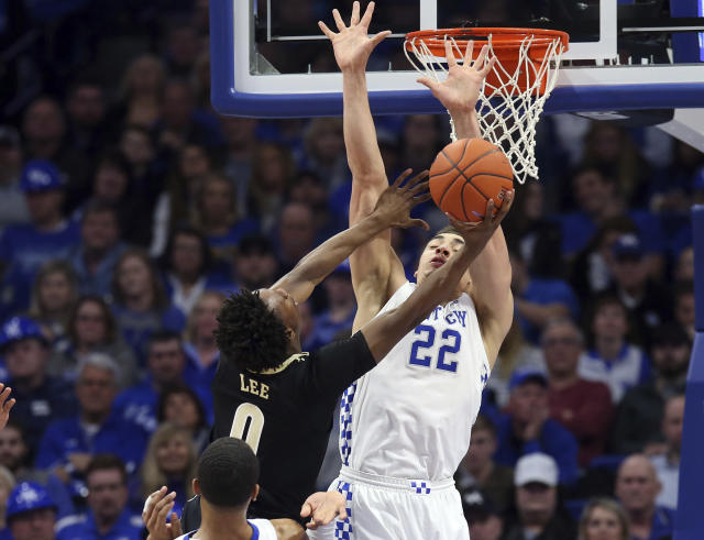 Vanderbilt's Saben Lee (0) shoots under pressure from Kentucky's Reid Travis (22) during the second half of an NCAA college basketball game in Lexington, Ky., Saturday, Jan. 12, 2019. (AP Photo/James Crisp)