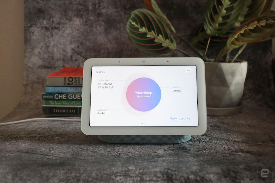 Google Nest Hub 2021 (2nd gen) photo. Picture of Google's newest smart display on a table with books and a plant in the background.