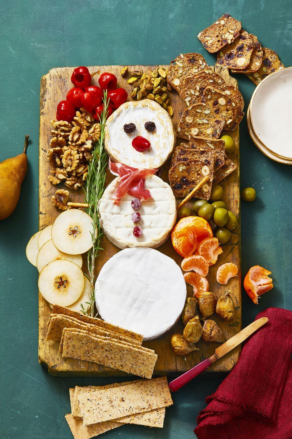 <p>To recreate this adorable holiday app, you'll need three cheese wheels, prosciutto for the scarf, sugared cranberry buttons, raisin eyes and a chile pepper nose. So easy, and so cute!</p>