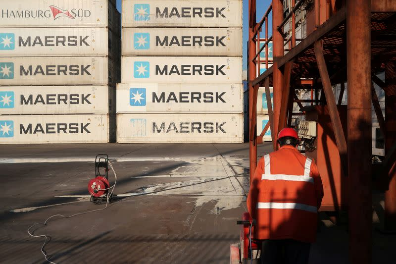Worker is seen next to Maersk shipping containers at a logistics center near Tianjin por