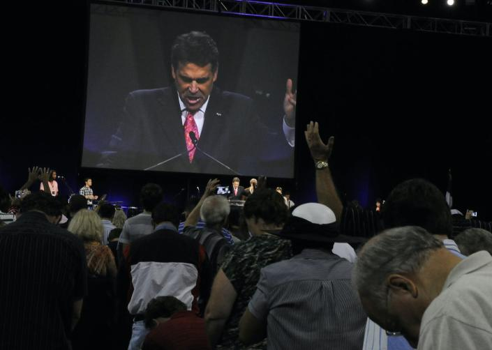 """<span class=""""caption"""">Worshipers pray with Texas Gov. Rick Perry, seen at center and on screen, at The Response, a daylong prayer and fast rally on Aug. 6, 2011, at Reliant Stadium in Houston.</span> <span class=""""attribution""""><span class=""""source"""">AP Photo/Pat Sullivan</span></span>"""
