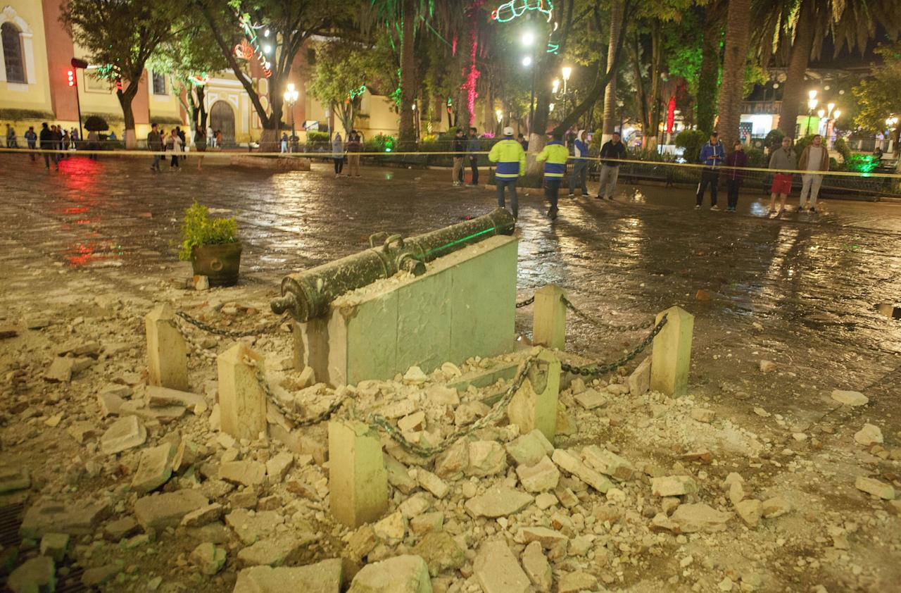 <p>A monument surrounded by debris is cordoned off in the aftermath. The earthquake has toppled houses and businesses and sent panicked people into the streets.(AP/REX/Shutterstock) </p>