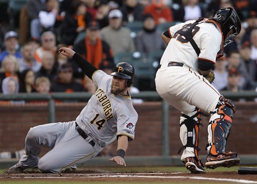 Pittsburgh Pirates' Casey McGehee, left, slides to score behind San Francisco Giants catcher Hector Sanchez during the first inning of a baseball game Saturday, April 14, 2012, in San Francisco. McGehee scored on a single by Neil Walker. (AP Photo/Ben Margot)