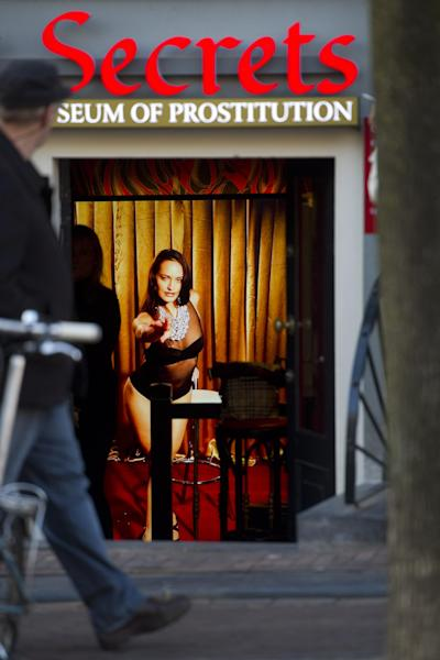 In this photo taken Tuesday, Feb. 4, 2014 a hologram of a beckoning prostitute is shown at the entrance of the 'Red Light Secrets' museum in Amsterdam. On any given evening, thousands of tourists stroll down the narrow streets of Amsterdam's famed Red Light District, gawking at ladies in lingerie who work behind windows, making a living selling sex for money. Now a small educational museum is opening in heart of the district that aims to show reality from the other side of the glass. Organizer Melcher de Wind says the Red Light Secrets museum is for those who want to learn more about how the area works without actually visiting a prostitute. (AP Photo/Evert Elzinga)