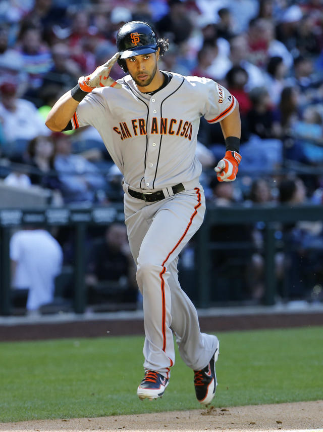 San Francisco Giants center fielder Angel Pagan salutes the Giants dugout as he rounds the bases after hitting a three-run home run against the Arizona Diamondbacks during the eighth inning of a baseball game Thursday, April 3, 2014, in Phoenix. (AP Photo/Matt York)